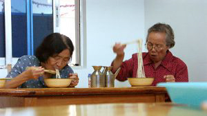 Two old ladies eating Lo Mein.