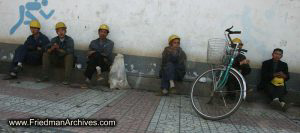 Construction workers sitting next to wall
